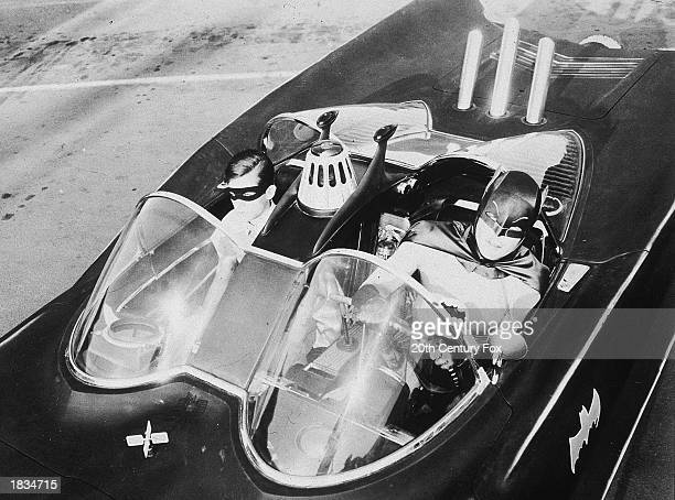 American actors Burt Ward as Robin and Adam West as Batman ride in the Batmobile in a still from the television series 'Batman' c 1967