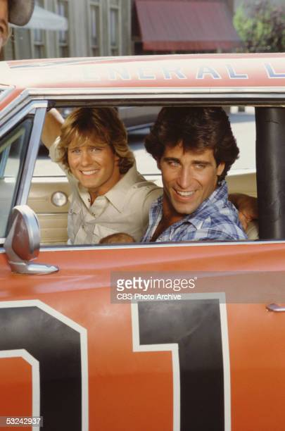 American actors Byron Cherry and Christopher Mayer sit in the 'General Lee,' the famous orange Dodge Charger from the television series 'The Dukes of...