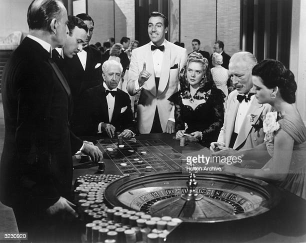 American actors Cesar Romero and Alice Faye gamble at a baccarat table at a casino in a still from director Walter Lang's film 'Weekend in Havana'