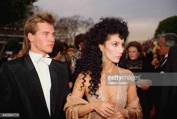 American actors Cher and Val Kilmer arrive at the 56th Academy Awards, where Cher is nominated for Best Supporting Actress in Silkwood.