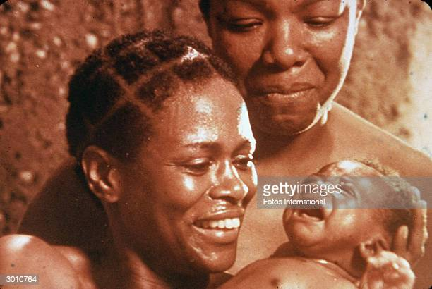 American actors Cicely Tyson and Maya Angelou look lovingly at a baby in a scene from the television mini series 'Roots' directed by Marvin J Chomsky...