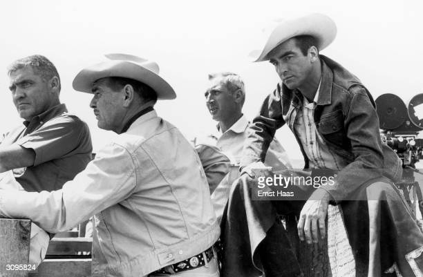 American actors Clark Gable and Montgomery Clift filming John Huston's 'The Misfits' on location in the Nevada Desert Between them is producer Frank...