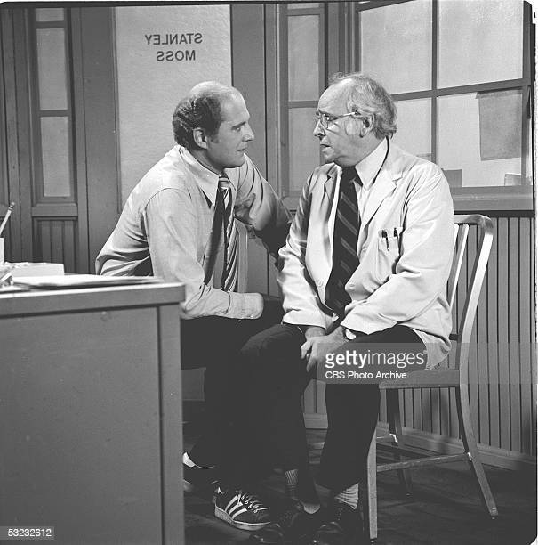American actors David Ogden Stiers and Barnard Hughes talk together as they sit at a desk in a scene from the CBS sitcom 'Doc' August 17 The series...