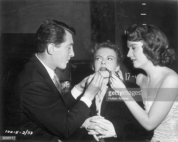 American actors Dean Martin and Polly Bergen apply actor Marion Marshall's lipstick on the set of director Hal Walker's film 'That's My Boy'