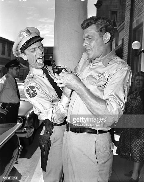 American actors Don Knotts and Andy Griffith struggle for a gun during an episode of the CBS rural sitcom 'The Andy Griffith Show' California 1960...