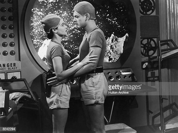 American actors Donna Martell and Ross Ford embrace in a still from director Richard Talmadge's science fiction film 'Project Moon Base'