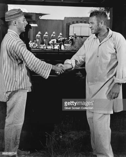 American actors Dustin Hoffman and Steve McQueen shake hands in a scene from 'Papillon' 1973
