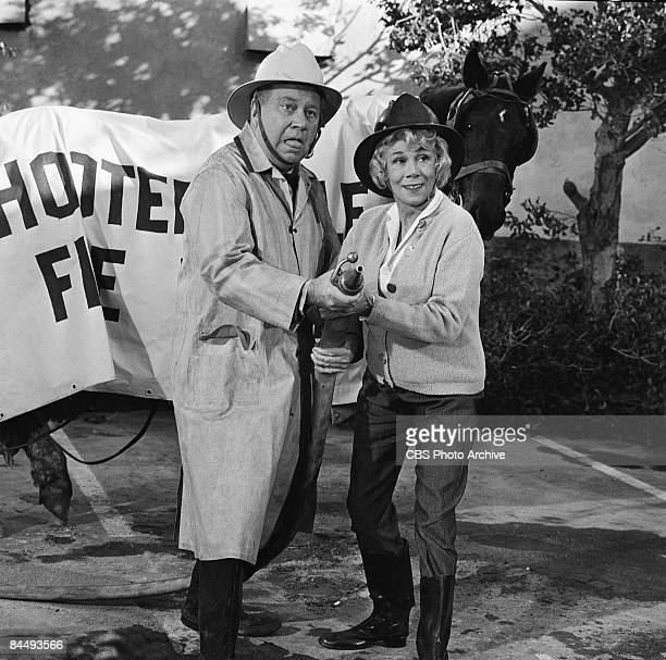 American actors Edgar Buchanan as Joseph P 'Uncle Joe' Carson and Bea Benaderet as Kate Bradley hold a firehose together in an episode of the...