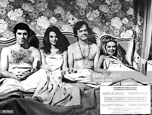 American actors Elliott Gould Natalie Wood Robert Culp and Dyan Cannon sit in bed together in a promotional still from the film 'Bob Carol Ted Alice'...