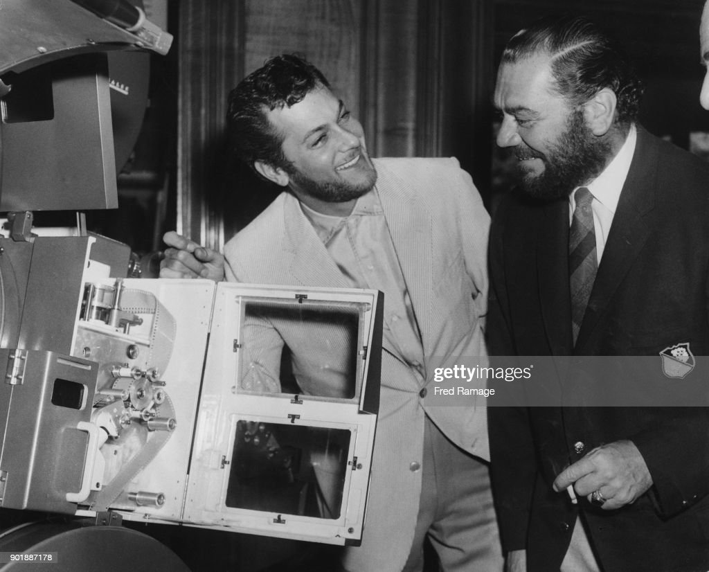 American actors Ernest Borgnine (1917 - 2012) and Tony Curtis (left) attend a demonstration of the Technirama projection system at the Odeon Cinema in Leicester Square, London, 1st June 1957. Both are wearing beards for their upcoming roles in the film 'The Vikings'.