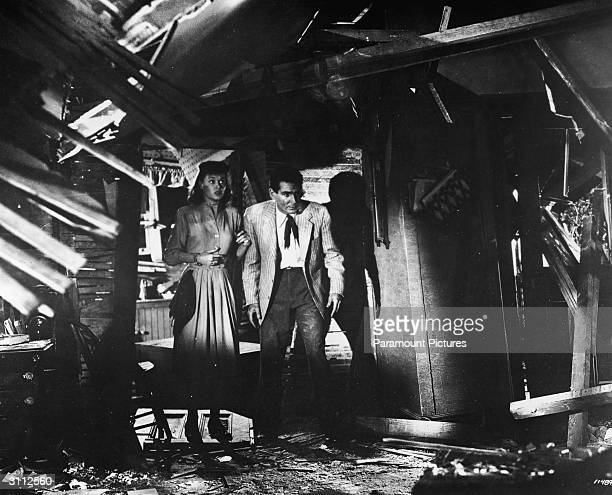 American actors Gene Barry and Ann Robinson investigate a dark room in a still from the film 'The War Of The Worlds' directed by Byron Haskin 1953