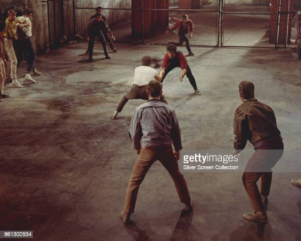 American actors George Chakiris and Russ Tamblyn , surrounded by cast members, fight in a scene from 'West Side Story' , 1961.