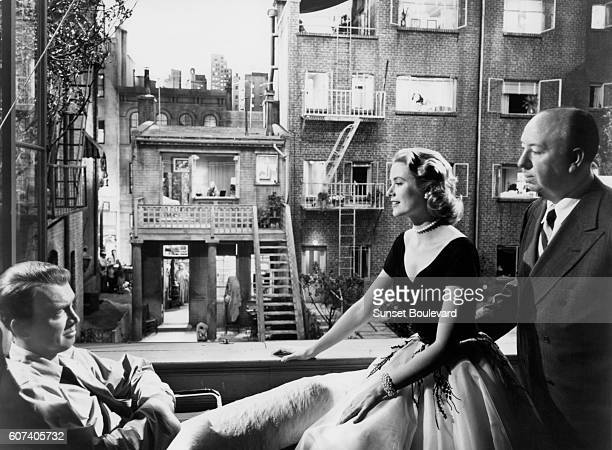 American actors Grace Kelly and James Stewart with British director and producer Alfred Hitchcock on the set of his movie Rear Window