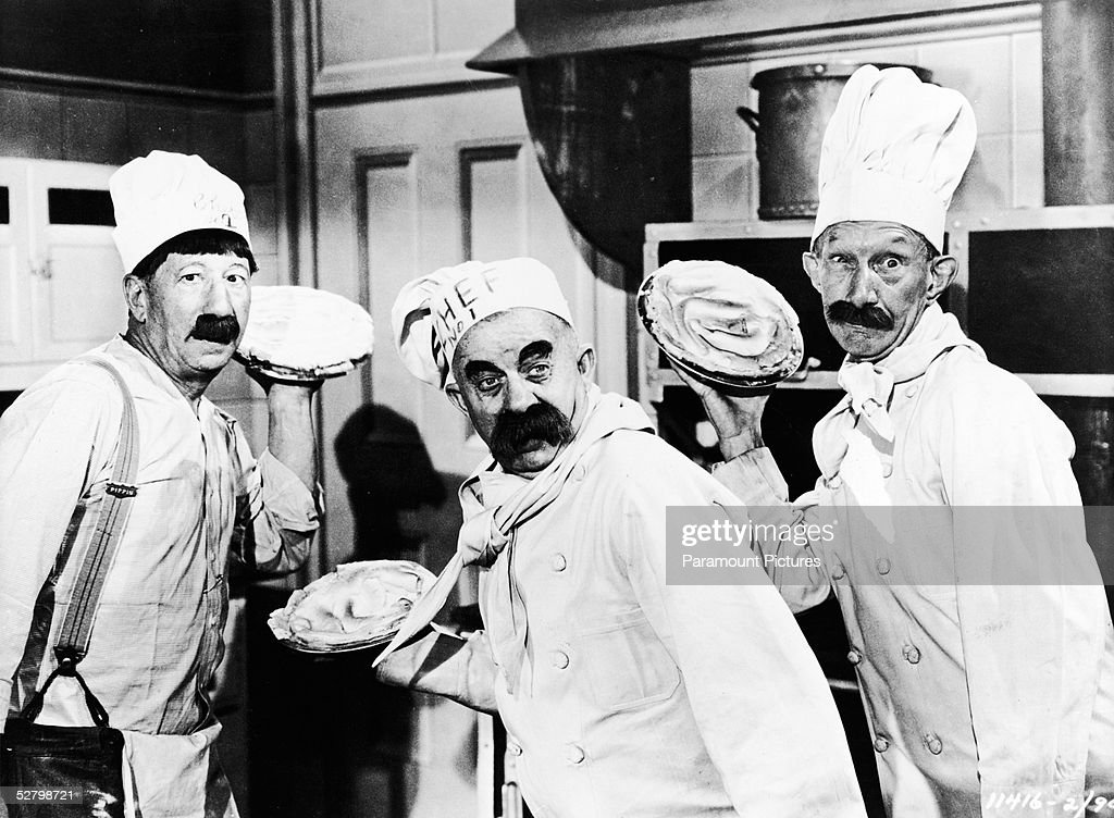 American actors (left to right) Hank Mann (1887 - 1971) and Chester Conklin (1886 - 1971) and Scottish-born actor James Finlayson (1887 - 1953) dress as chefs and prepare to throw pies in a still from 'The Perils of Pauline' directed by George Marshall, 1947. The film follows a woman as she tries to find work in Silent Era Hollywood and includes many stars from that time.