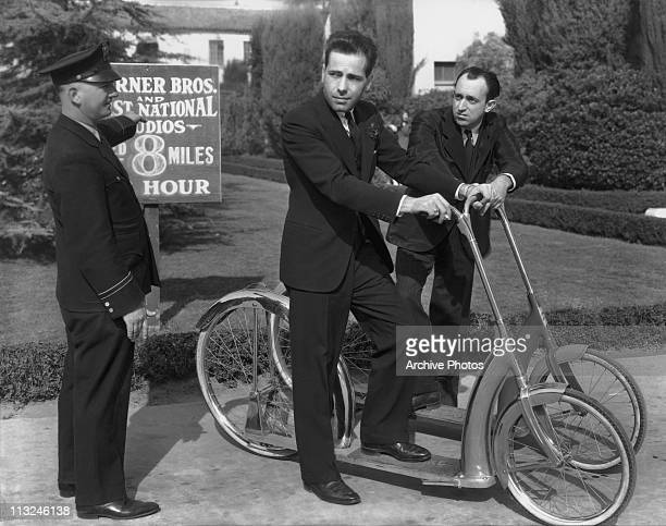 American actors Humphrey Bogart and Allen Jenkins are stopped for speeding on their scooters by a security guard at the Warner Bros. Studios circa...