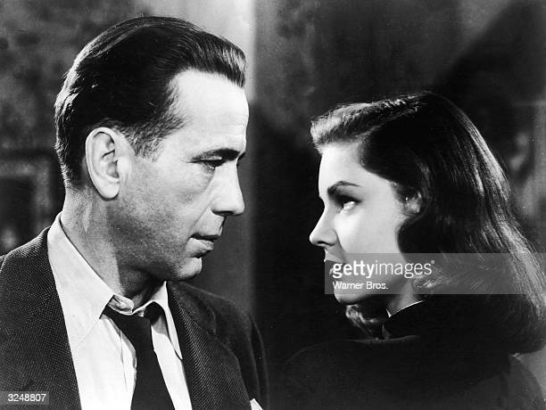American actors Humphrey Bogart and Lauren Bacall look into each other's eyes in a still from director Howard Hawks' film, 'The Big Sleep.'