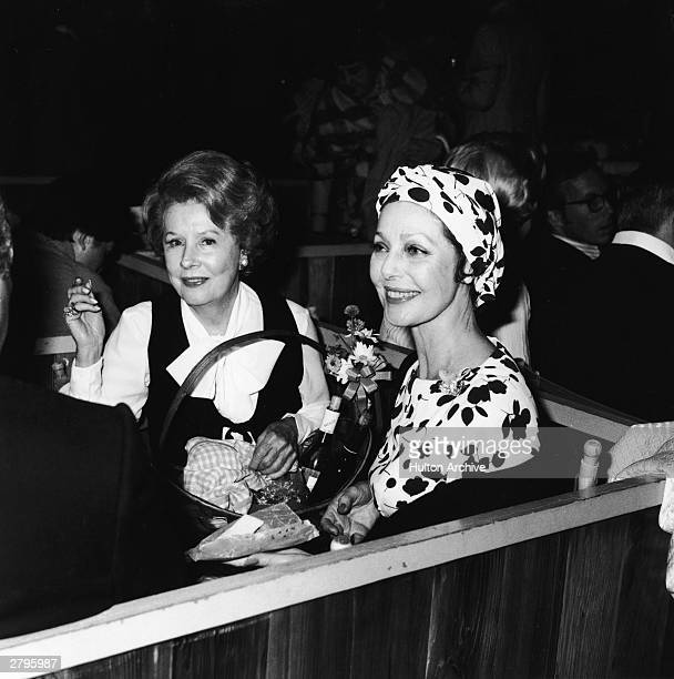 American actors Irene Dunne and Loretta Young eat a meal from a picnic basket while attending a charity event at the Hollywood Bowl in Hollywood...