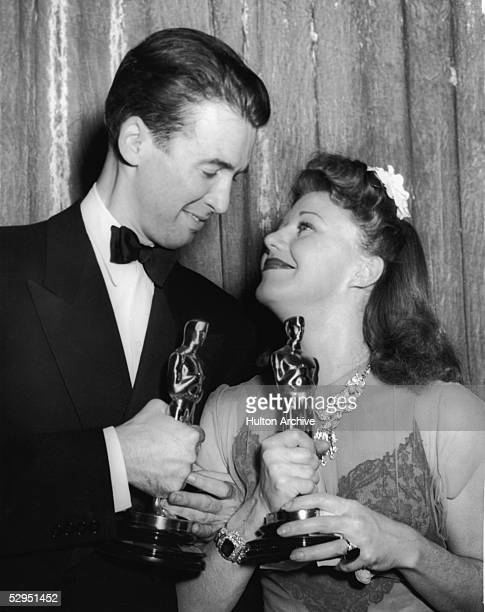 American actors James Stewart and Ginger Rogers arms locked and Oscars in hand gaze into each other's eyes at the 1940 Academy Awards banquet Los...