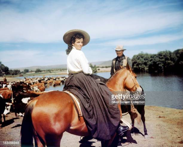 American actors Jane Russell and Clark Gable on horseback in a cattle drive scene from 'The Tall Men' directed by Raoul Walsh 1955