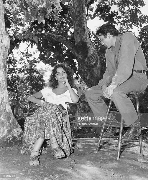 American actors Jennifer Jones and Gregory Peck relax under a tree on the set of director King Vidor's film 'Duel In The Sun'