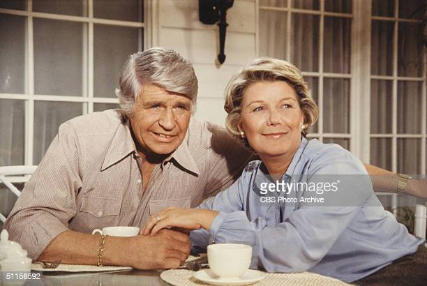 American actors Jim Davis and Barbara Bel Geddes, as John Ross 'Jock' Ewing and Eleanor Southworth 'Miss Ellie' Ewing, sit at a table on a porch as...