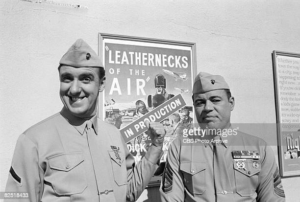 American actors Jim Nabors and Frank Sutton pose near a movie poster in a scene from an episode of the television comedy series 'Gomer Pyle USMC'...