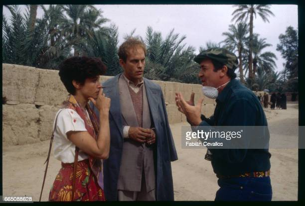 American actors John Malkovitch and Debra Winger listen to film director Bernardo Bertolucci's indications during the shooting of the movie Un The au...