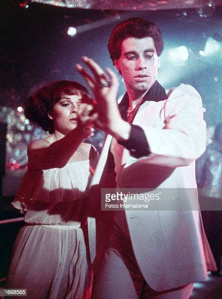 American actors John Travolta wearing a white suit with a black shirt and Karen Lynn Gorney disco dance in a still from the film 'Saturday Night...