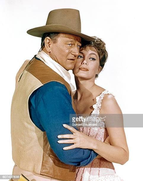 American actors John Wayne and Charlene Holt on the set of El Dorado based on the novel by Harry Brown and directed by Howard Hawks