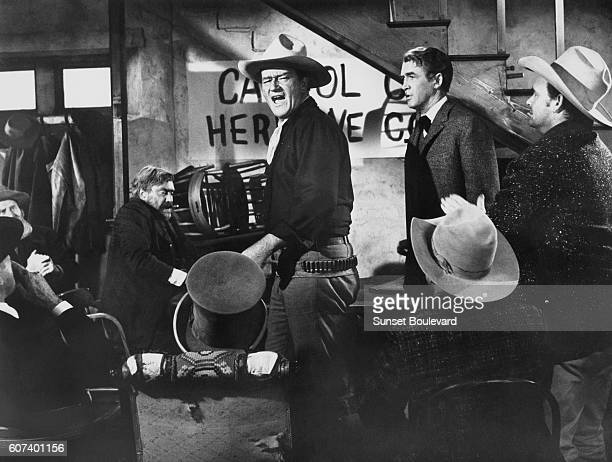American actors John Wayne and James Stewart on the set of The Man Who Shot Liberty Valance directed and produced by John Ford