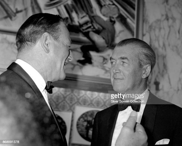 American actors John Wayne and James Stewart talk together at the Warner Hollywood Theatre for the premiere of 'How the West Was Won' Los Angeles...