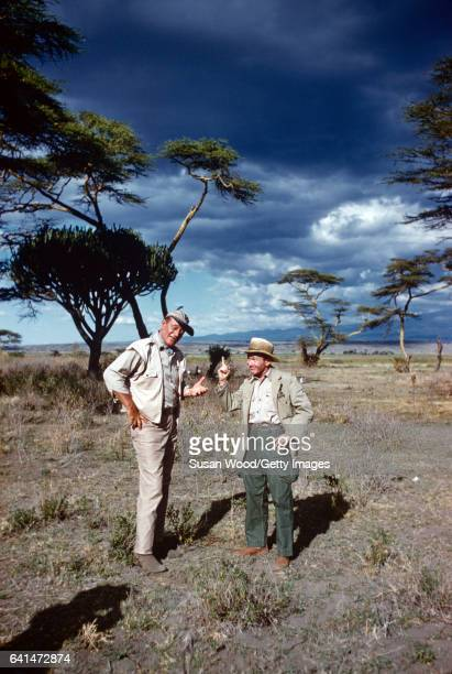 American actors John Wayne and Red Buttons talk together during a break in filming 'Hatari' Tanzania 1962