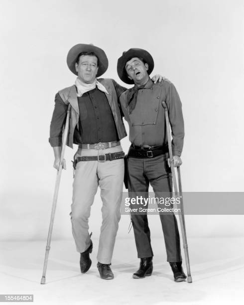 American actors John Wayne and Robert Mitchum on crutches in a promotional portrait for 'El Dorado' directed by Howard Hawks 1966