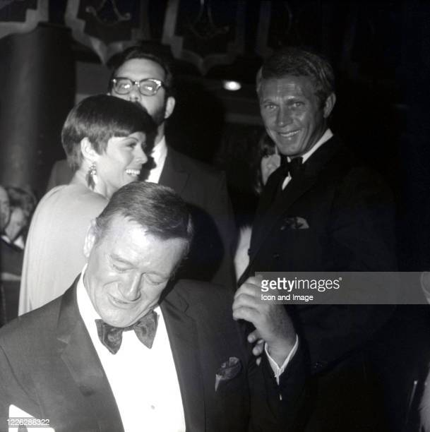 American actors John Wayne and Steve McQueen and FilipinaAmerican actress singer and dancer Neile Adams during the 24th Annual Golden Globe Awards at...