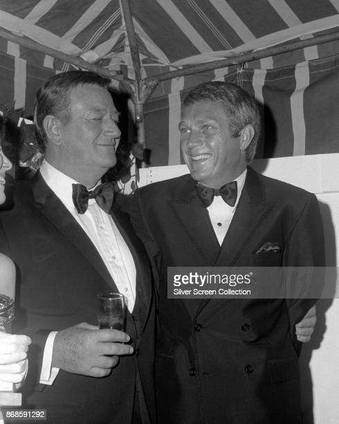 American actors John Wayne and Steve McQueen share a laugh during the 24th Annual Golden Globe Awards ceremony at the Cocoanut Grove Los Angeles...