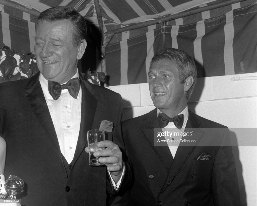American actors John Wayne (1907 - 1979) and Steve McQueen (1930 - 1980) share a laugh during the 24th Annual Golden Globe Awards ceremony at the Cocoanut Grove, Los Angeles, California, February 15, 1967.