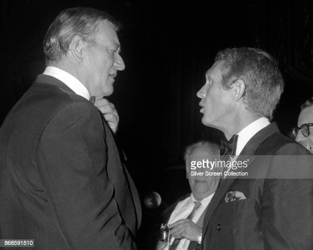 American actors John Wayne and Steve McQueen talk together during the 24th Annual Golden Globe Awards ceremony at the Cocoanut Grove Los Angeles...