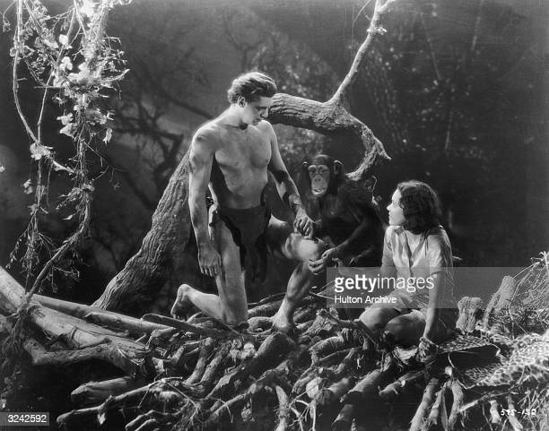 American actors Johnny Weissmuller as Tarzan and Maureen O'Sullivan as Jane hold hands with 'Cheetah' the chimpanzee in a still from director Cedric...