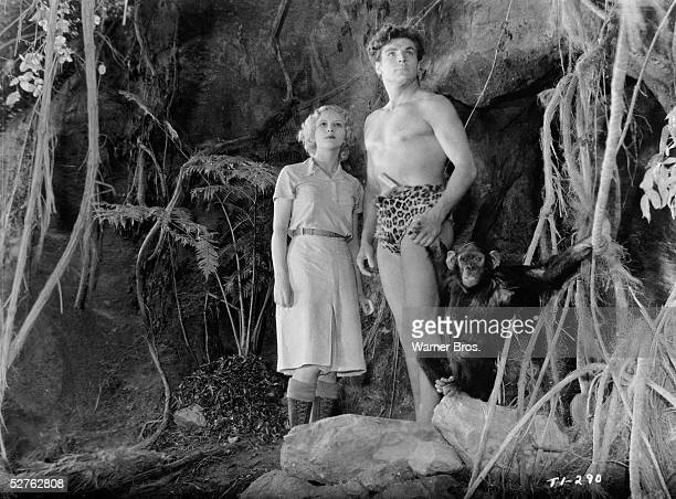 American actors Julie Bishop Buster Crabbe and a chimpanzee stand at the mouth of a cave and gaze with determination into the distance in a scene...
