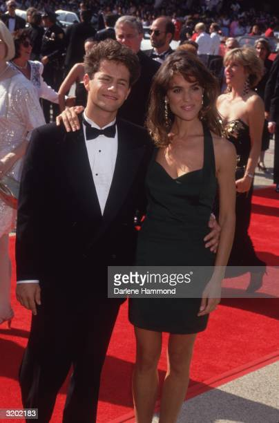 American actors Kirk Cameron and Chelsea Noble stand with their arms around each other on the red carpet at the Emmy Awards