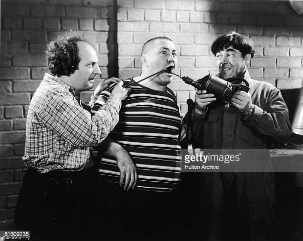 American actors Larry Fine and Moe Howard abuse Curly Howard with tools in a still from an unidentified Three Stooges film
