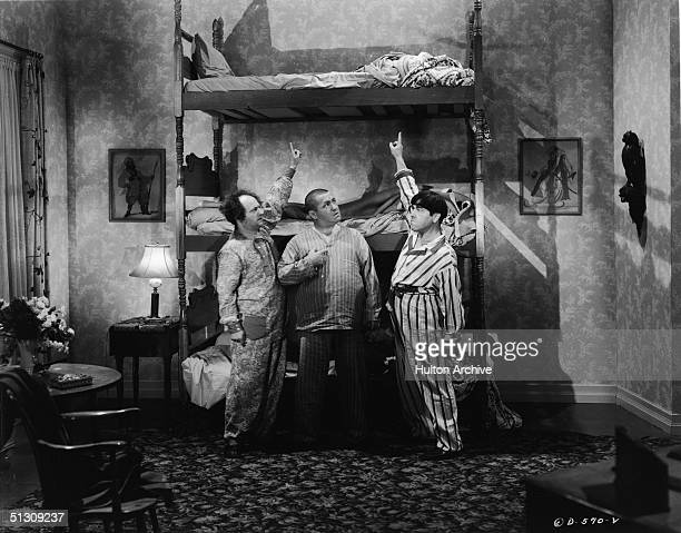 American actors Larry Fine and Moe Howard send Curly Howard to the top bunk in a still from an unidentified Three Stooges film