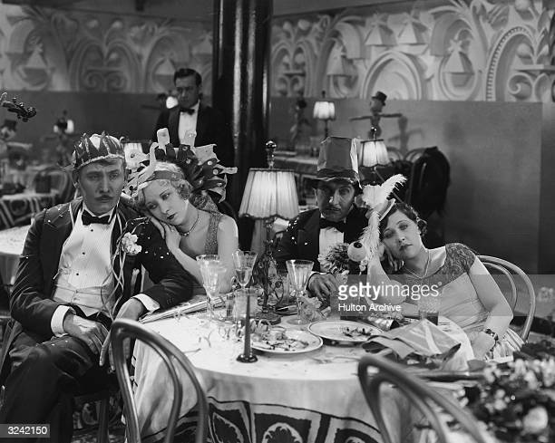 American actors Lew Cody Gwen Lee Roy D'Arcy and Gertrude Short look sad in their party hats while sitting in an empty restaurant in a still from...