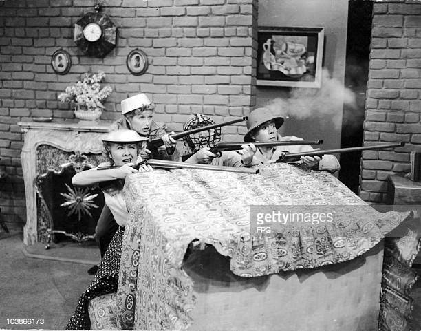 American actors Lucille Ball , Desi Arnaz, Vivian Vance and William Frawley defend their living room against invaders in 'New Neighbours', an episode...