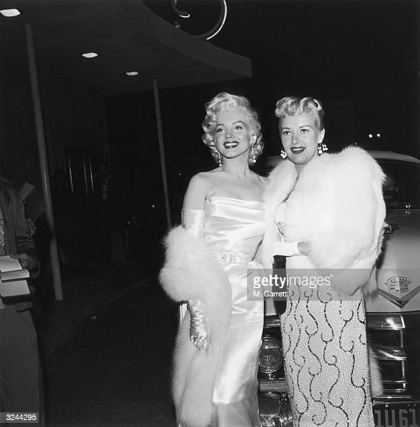 American actors Marilyn Monroe and Betty Grable at the premiere of director Jean Negulesco's film 'How to Marry a Millionaire' Monroe is wearing a...