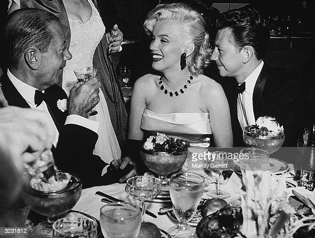 American actors Marilyn Monroe and Donald O'Connor sitting and talking with American composer and lyricist Cole Porter at a dining table at a...
