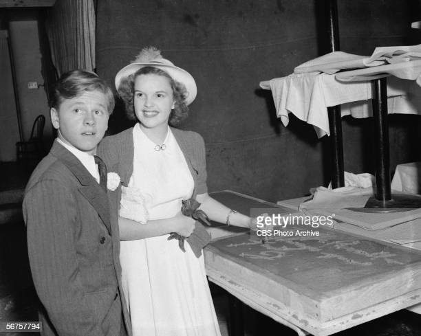 American actors Mickey Rooney Judy Garland sign their names in cement following the first Screen Guild Theatre broadcast at the Earl Carroll Theatre...