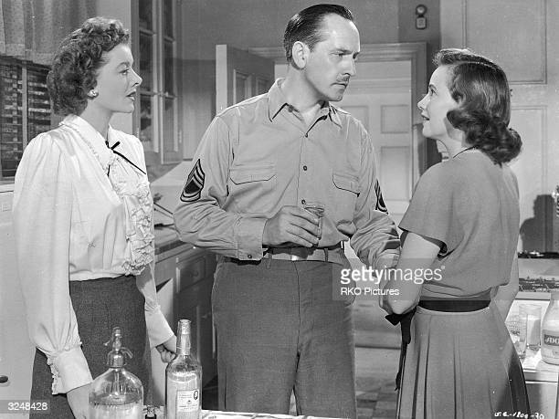 American actors Myrna Loy and Teresa Wright with Fredric March holding a glass of liquor in a still from the film 'The Best Years of Our Lives'...