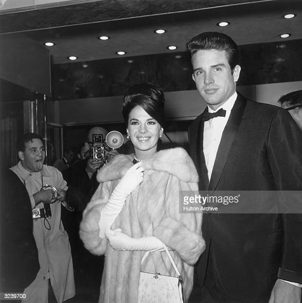 American actors Natalie Wood and Warren Beatty smile as they attend the premiere of director David Lean's film 'Lawrence of Arabia' Wood wears a fur...