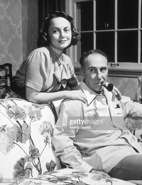 American actors Olivia de Havilland and Marcus Goodrich at their home in Los Angeles California Goodrich is seated on a couch smoking a pipe and his...